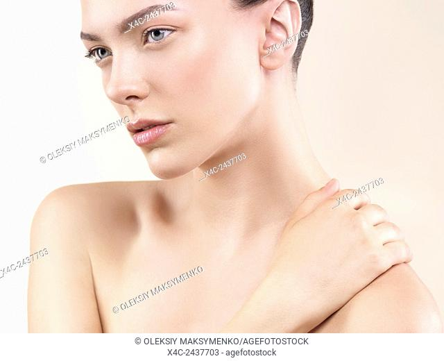 Closeup face beauty portrait of a young woman with clean natural look and perfect skin on beige background