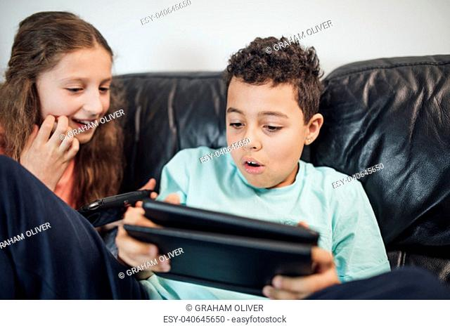Little boy and his sister are playing on handheld game consoles at home