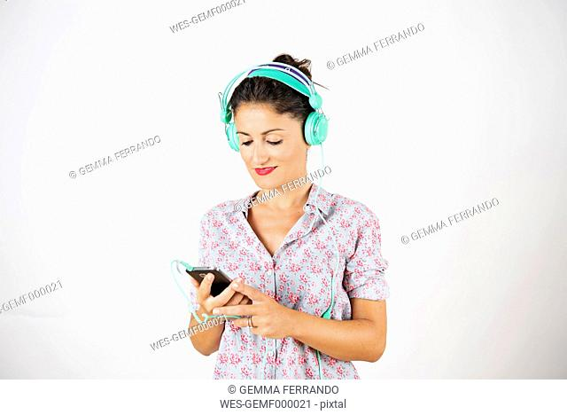 Woman with smartphone and headphones listening music