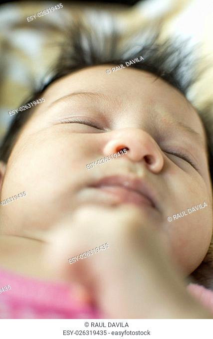 Newborn girl sleeping on a blanket with a calm expression