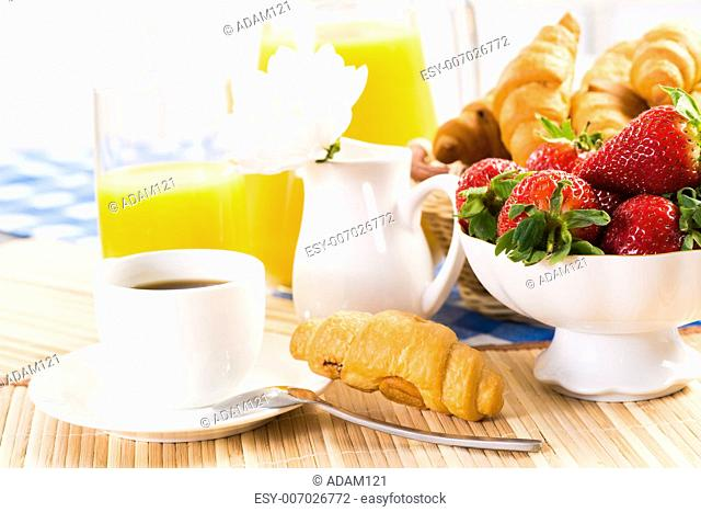 continental breakfast: coffee, strawberry, croissant and juice