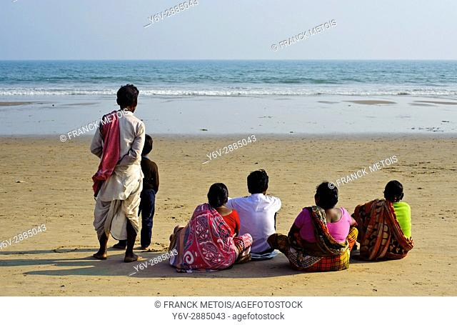 Indian family watching the sea ( i. e. the bay of Bengal at Puri, India)