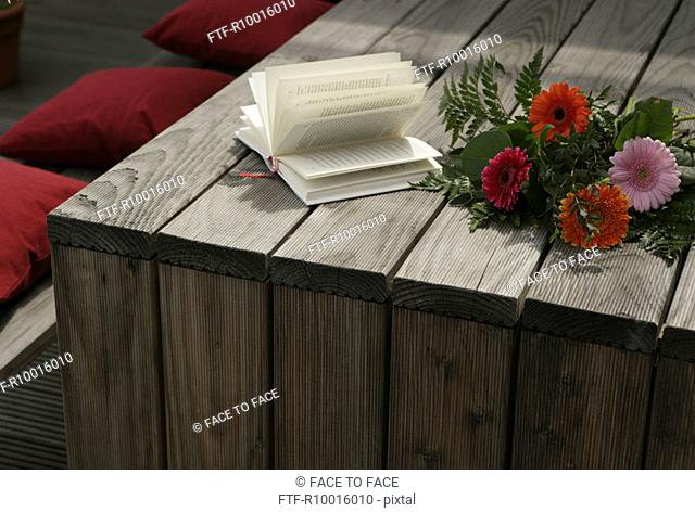 Bunch of Flowers, flower and a novel seen on a wooden table with some red cushions beside it
