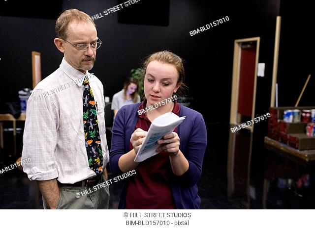 Student and teacher reading script in high school drama class