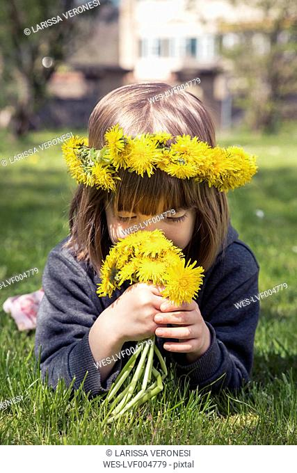 Little girl with floral wreath lying on meadow smelling dandelions