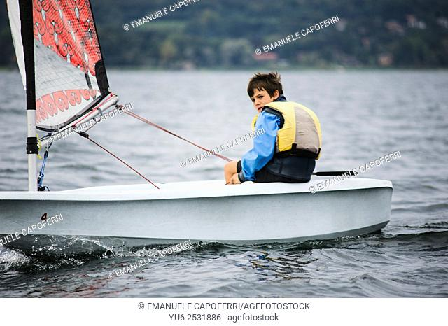 Child sailing on sailboat in the waters of Lake Maggiore, Ispra, Varese, Lombardy, Italy