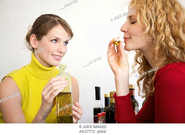 Two women tasting a sample of olive oil