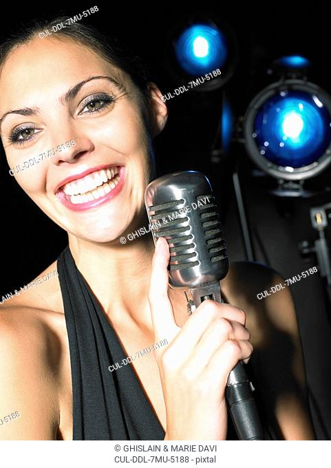 Woman smiling and holding microphone
