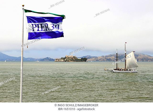 Flag of pier 39 and a historic sailboat in the San Francisco Bay, Alcatraz Island at the back, San Francisco, California, USA, America