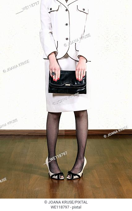 a woman in a vintage skirt suit is holding a black handbag