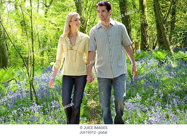 Couple walking in field of bluebell flowers