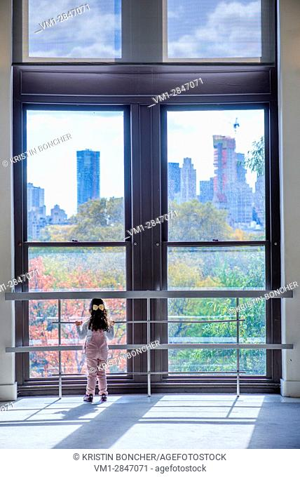 Girl looking out window to Central Park