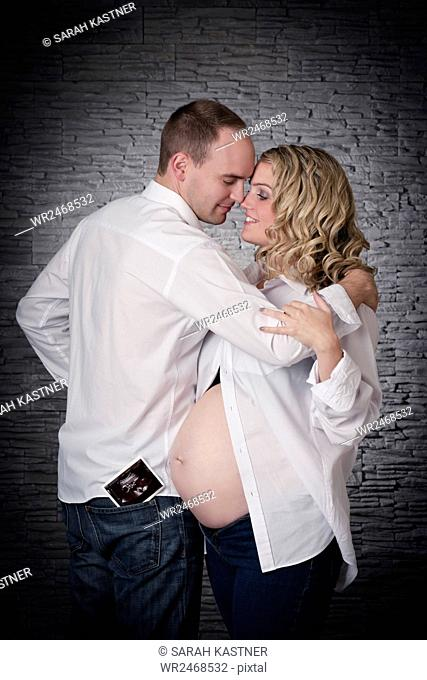 Pregnant woman and man hugging each other