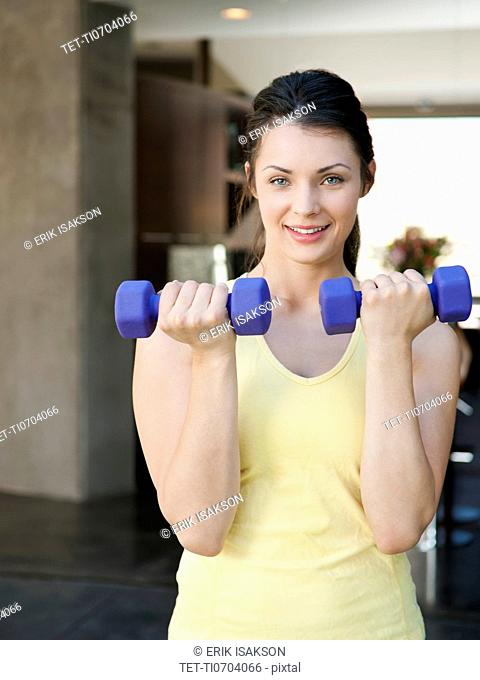 Young attractive woman exercising with dumbbells