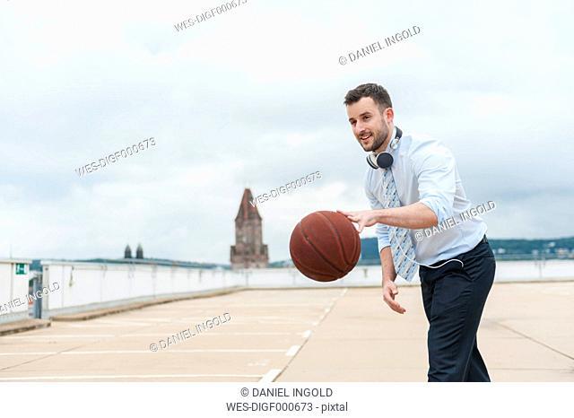 Businessman playing basketball outdoors