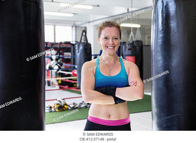 Portrait smiling, confident female boxer standing at punching bags in gym