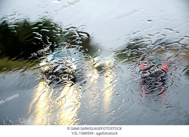 Traffic on countryside road under rain, drops on windscreen
