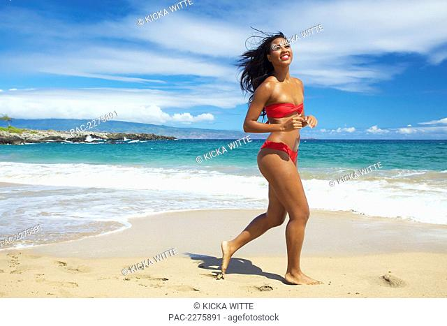 A young woman in a red bikini running on the beach of an hawaiian island; Maui, Hawaii, United States of America