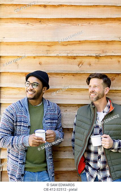 Smiling men drinking coffee outside cabin