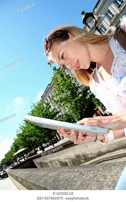 Blond woman in town using electronic tablet