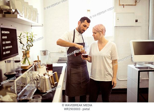 Male barista pouring black coffee in cup