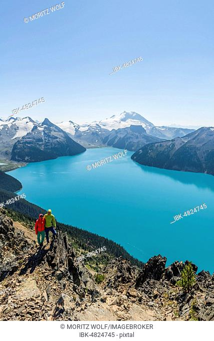 View from Panorama Ridge trail, two hikers on a rock, Garibaldi Lake, turquoise glacial lake, Guard Mountain and Deception Peak, rear glacier