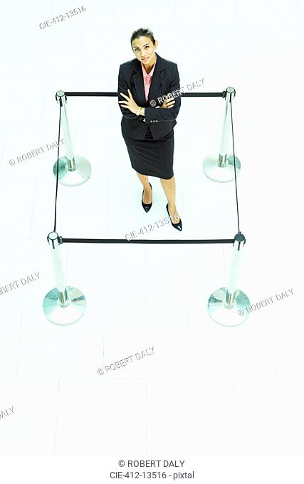 Businesswoman standing in roped-off square