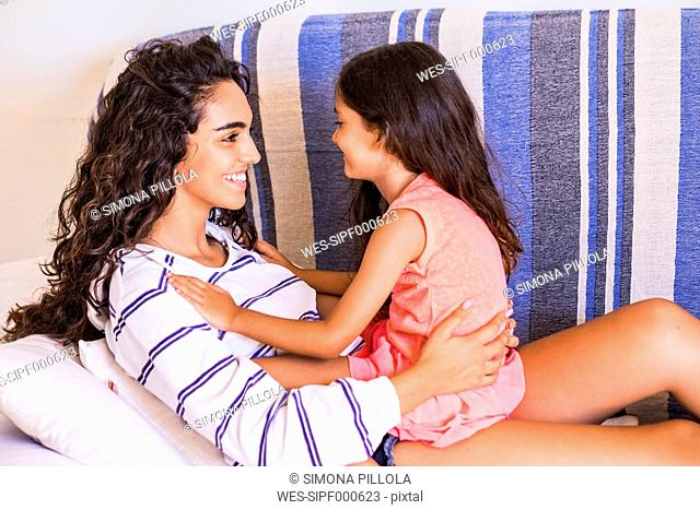 Smiling teenage girl and her little sister facing each other