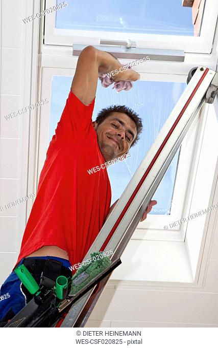 Germany, Window cleaner cleaning roof window