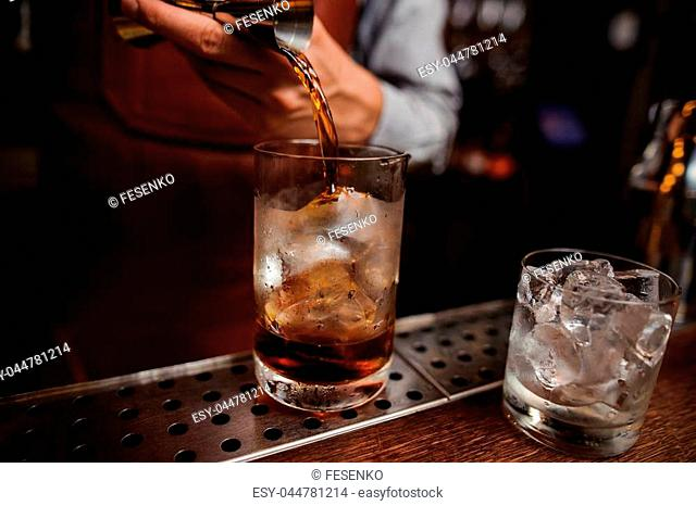 Close up shot of barman hand pouring drink from measuring cup into a cocktail glass filled with ice cubes. Male bartender preparing fresh cocktail