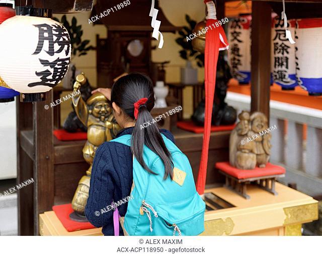 A girl patting Daikoku, one of the Seven Lucky Gods, a deity bringing wealth, at Jishu Jinja Shinto shrine of Kiyomizu-dera Buddhist temple in Higashiyama