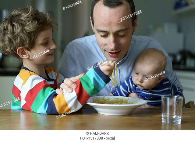 Boy feeding noodles to father carrying son at table