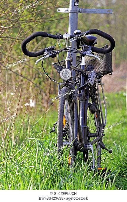 parked bike in grass locked at a sign pole, Germany
