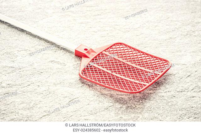 Fly swatter on stone table. Concept of exterminating bugs and insects