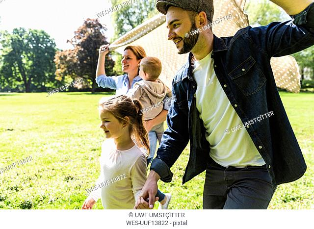 Happy family walking with a blanket in a park