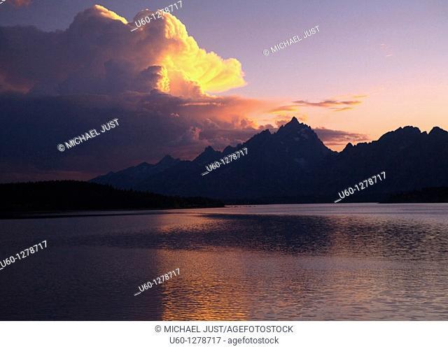 The setting sun shines over The Tetons Mountain Range and Jackson Lake at Grand Teton National Park, Wyoming