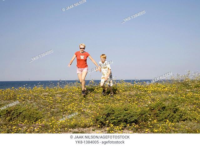 Woman and Kid Running Hand in Hand on Saaremaa Coast, Saare County, Estonia