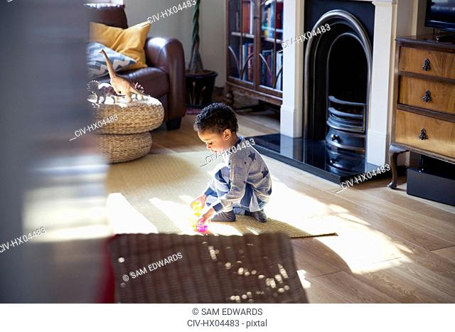 Boy in pajamas playing with toys on living room floor