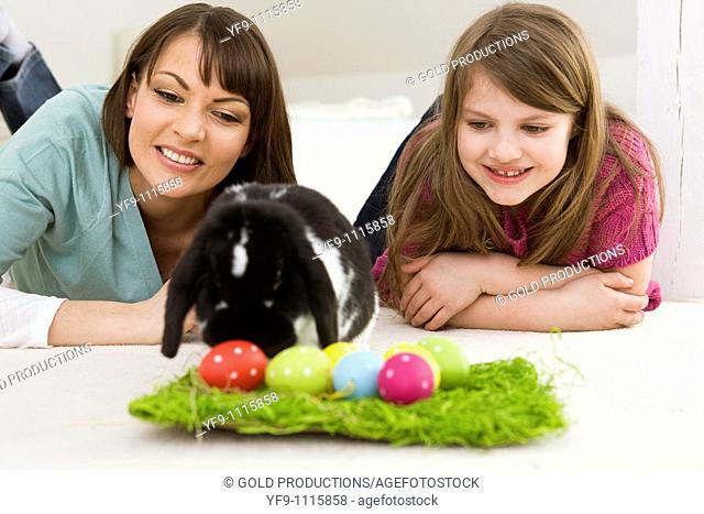 Mother and daughter with Easter Eggs and rabbit