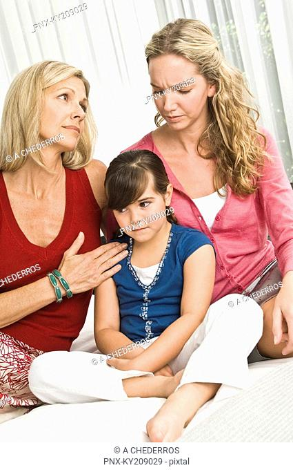 Girl sitting with her parents and looking sad