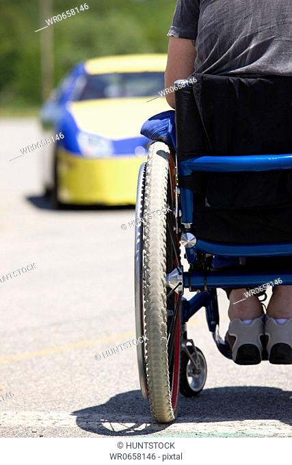 Person on wheelchair facing racing car, rear view