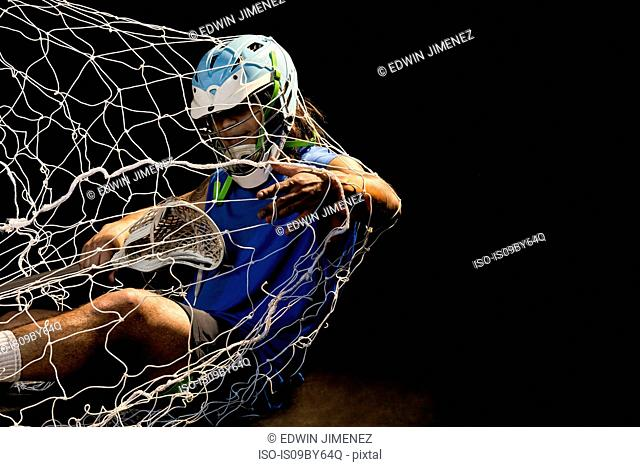 Young male lacrosse player in action falling into net, against black background