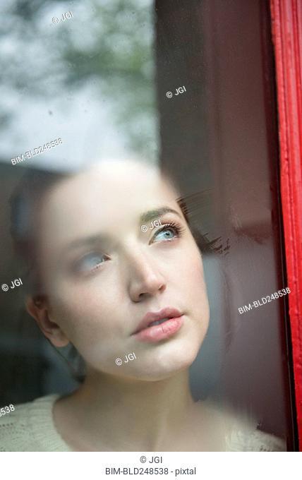 Caucasian woman daydreaming behind foggy window