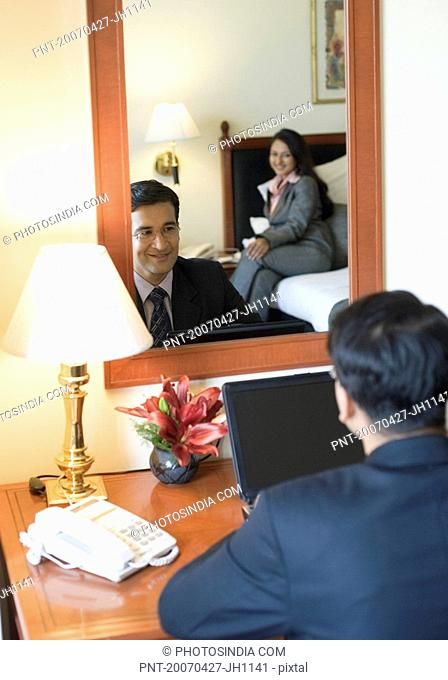 Rea view of a businessman using a laptop in front of a mirror