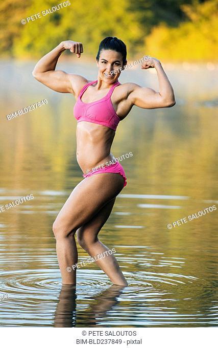 Mixed Race woman flexing muscles in lake