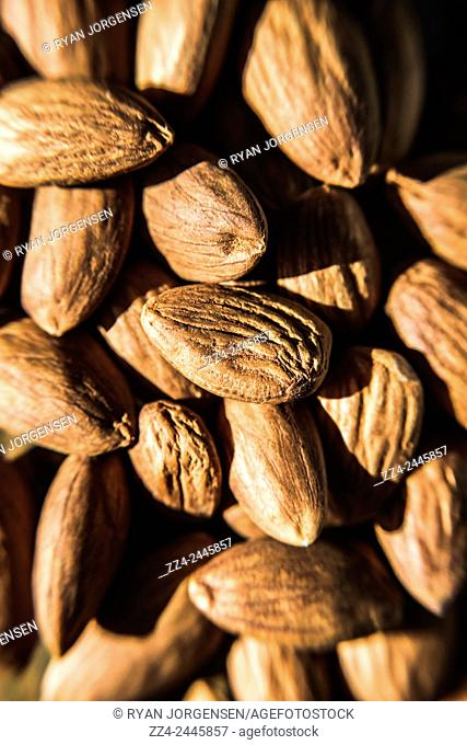 Close-up vertical food still on a pile of peeled almond nuts. Organic foods