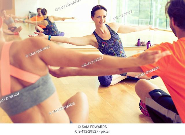 Fitness instructor with arms outstretched leading class in studio