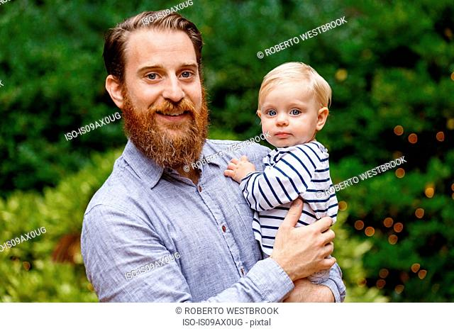 Portrait of father holding baby girl, outdoors, smiling