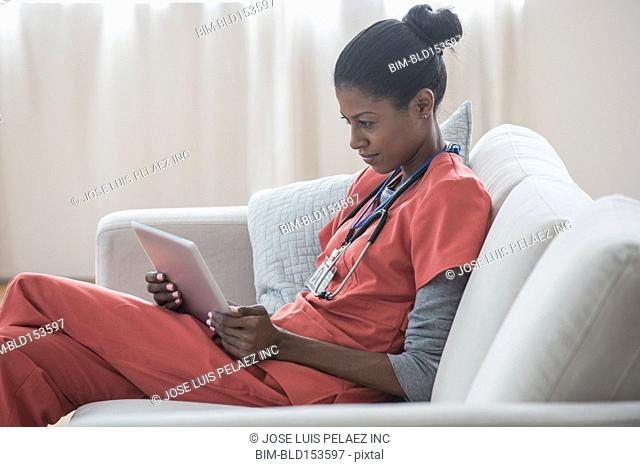 Nurse using digital tablet on sofa