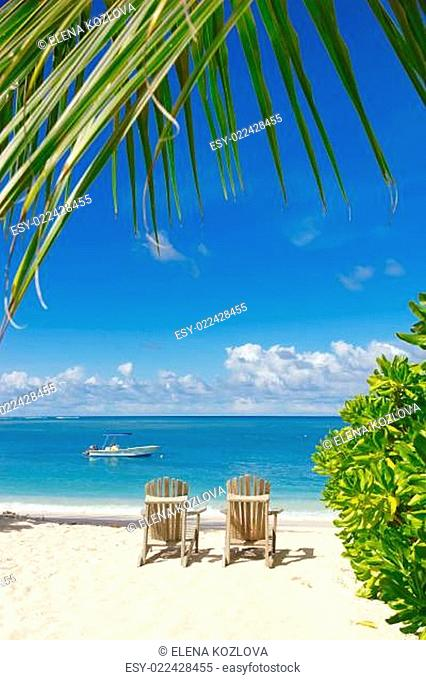 Beach chairs on white sand with blue sky background